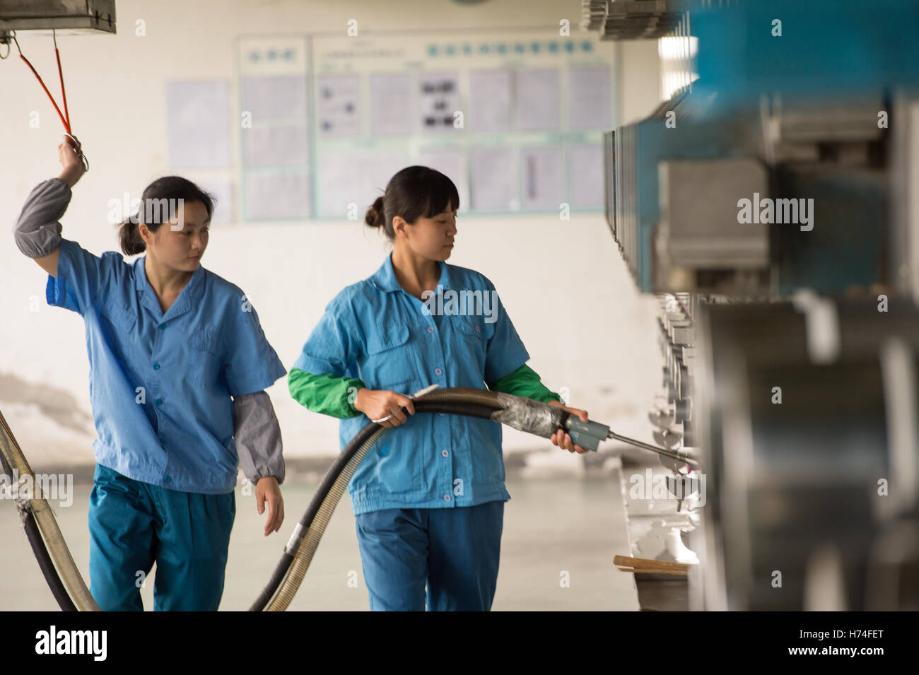 Woman using atomiser in textile factory - Stock Image