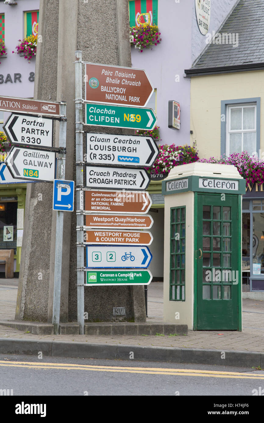Traditional Telefon - Telephone Cabin and Street Direction Signs, Westport; Ireland - Stock Image