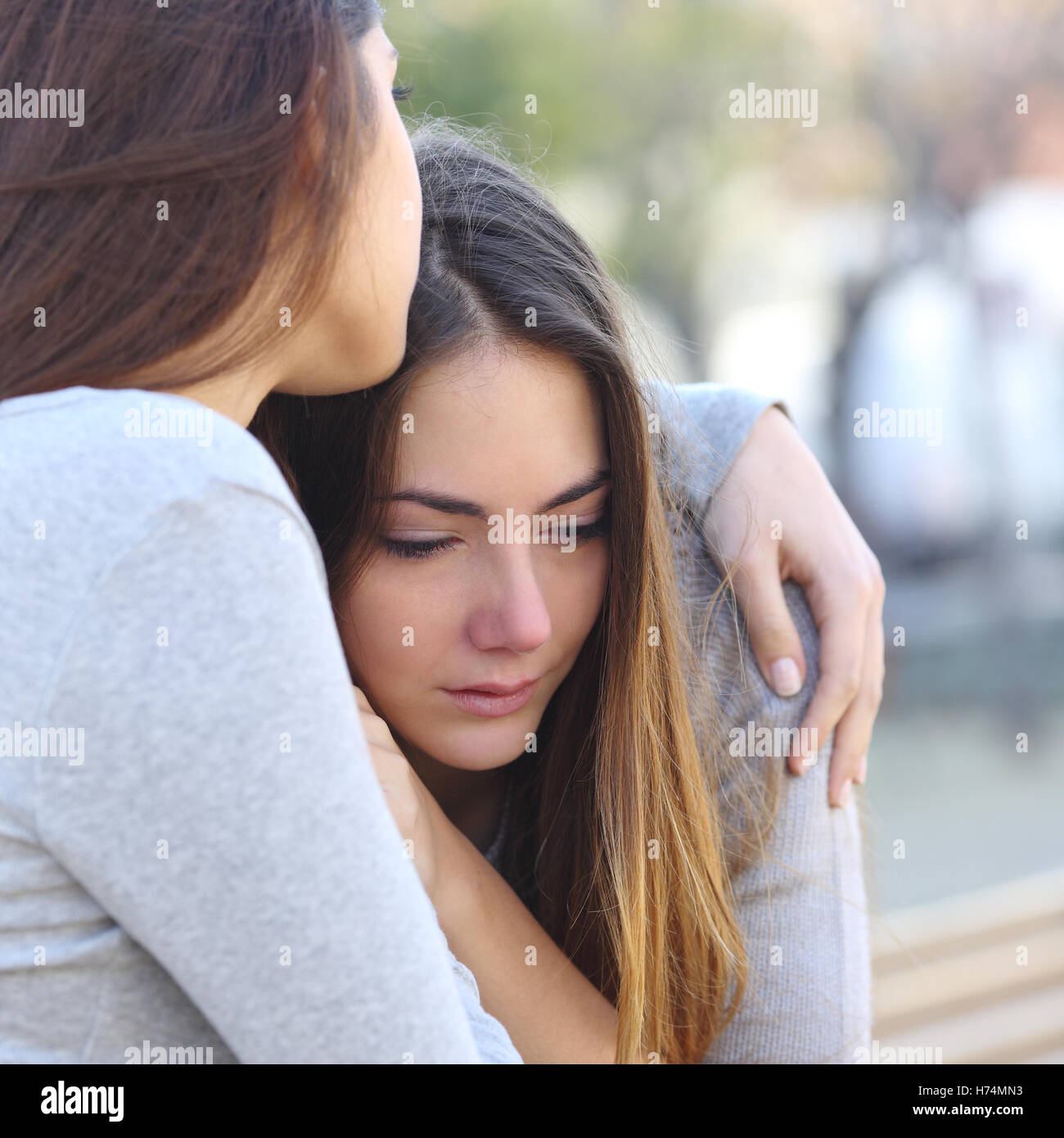 Sad girl crying and a friend comforting her - Stock Image