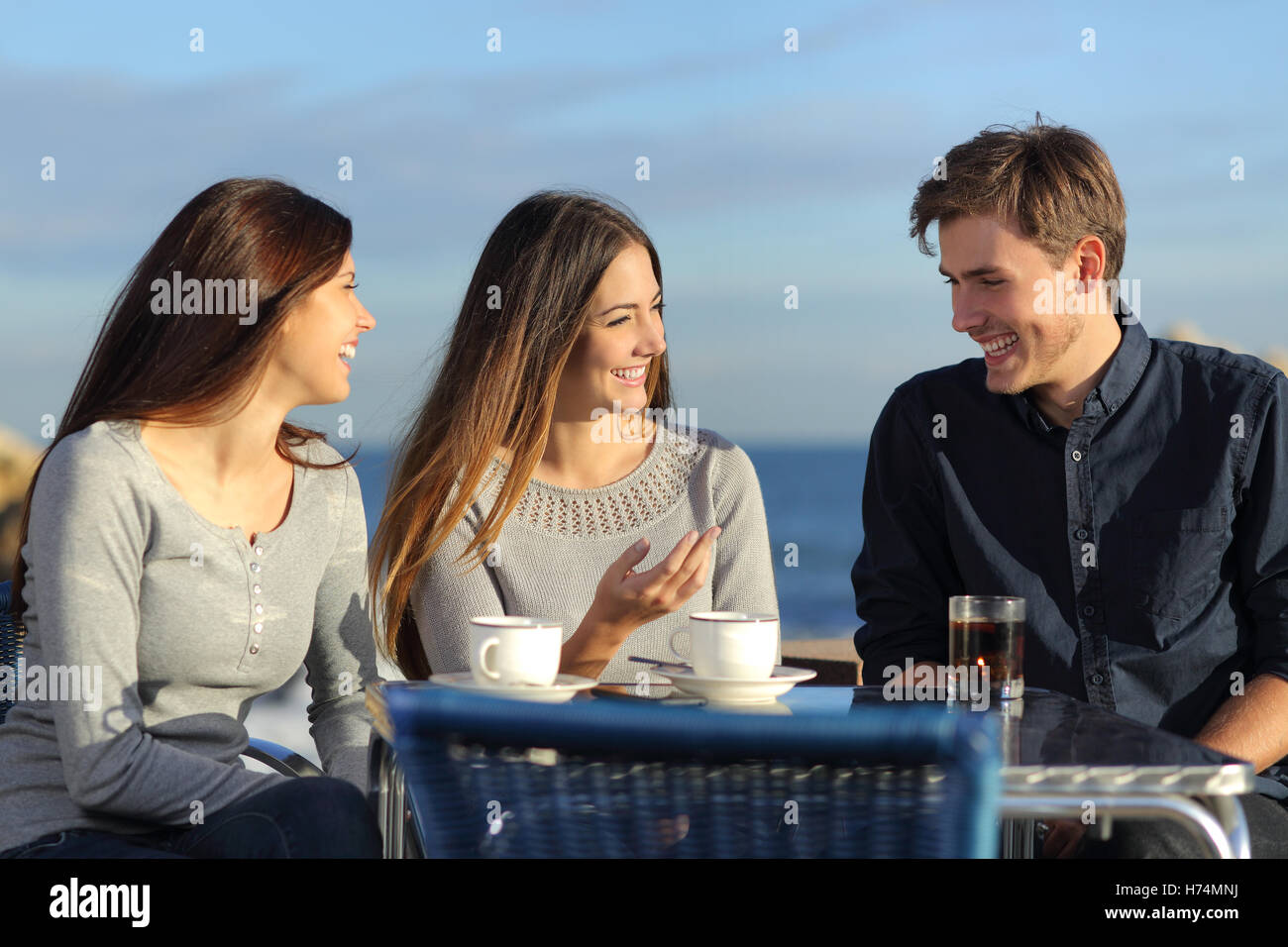 Friends talking in a restaurant on the beach Stock Photo