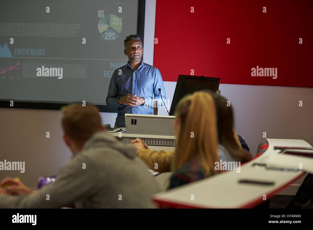 Lecture in a darkened university lecture theatre, student POV - Stock Image