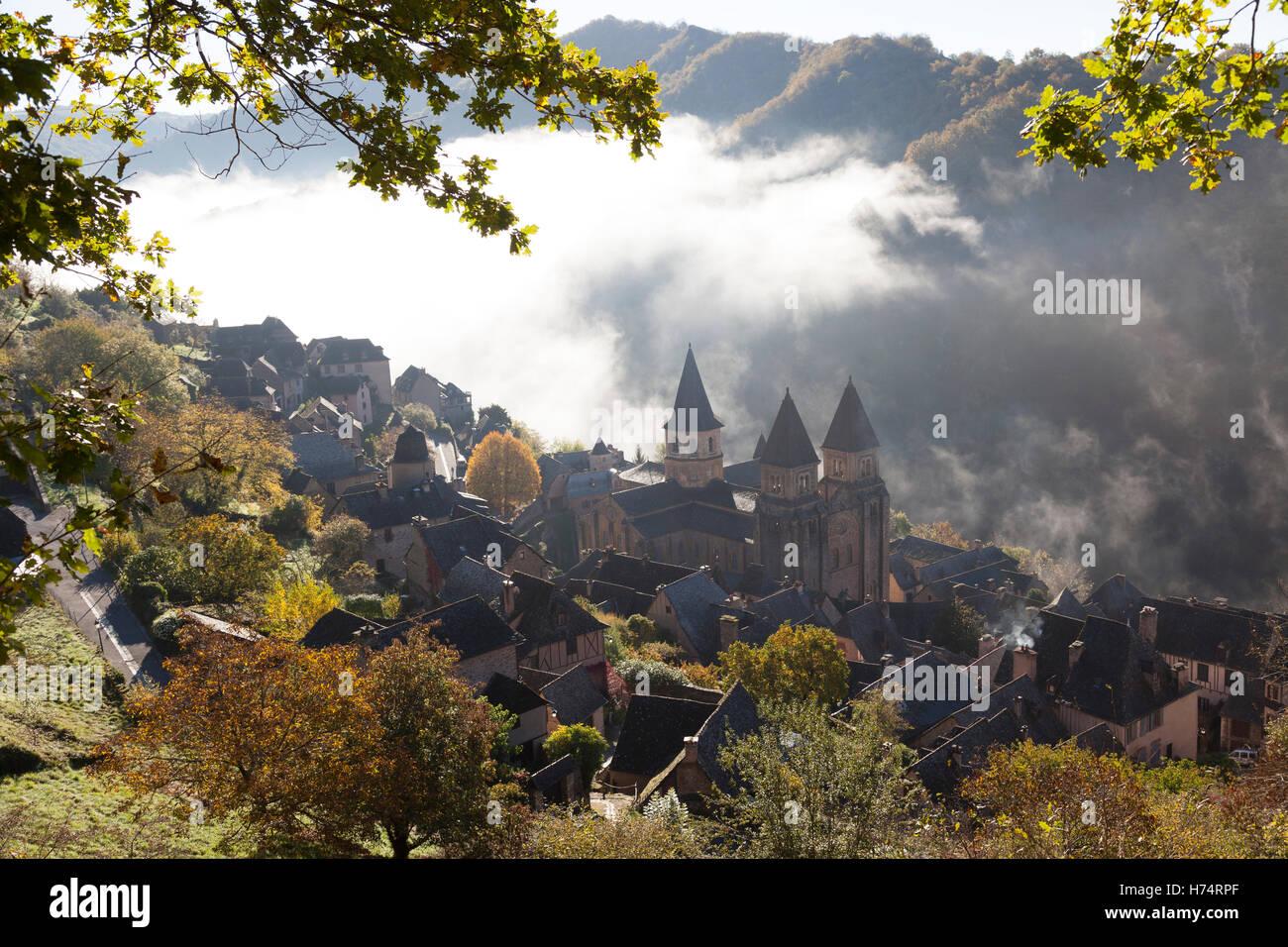 A high-angle shot on Conques (France), by a misty Autumnal morning. Contre-plongée sur Conques par un matin - Stock Image