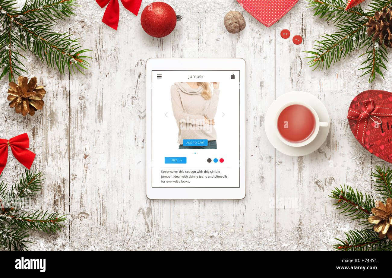 online shopping with tablet in christmas sale time top view of table with christmas decorations buying jumper on commerce webs