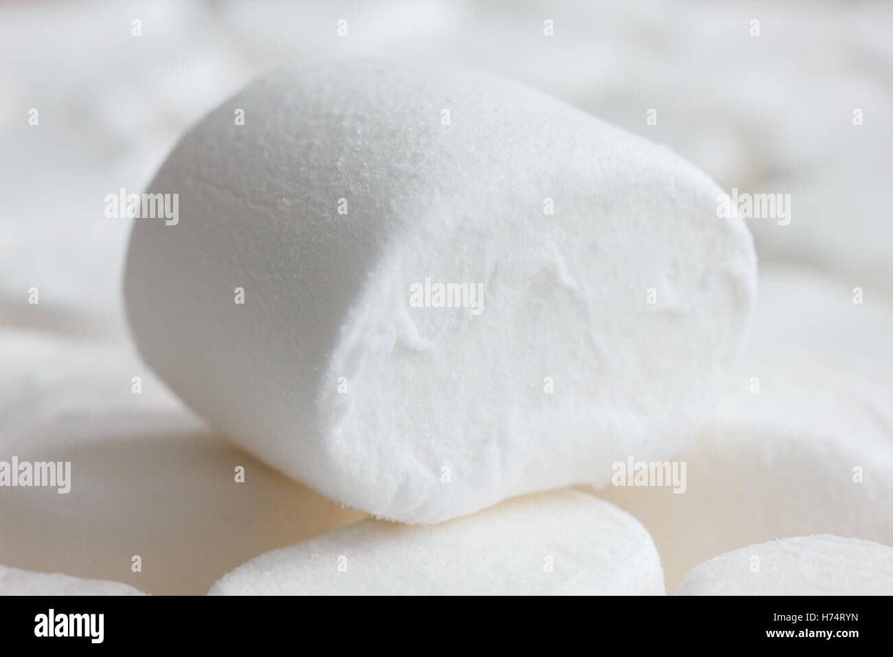 Single white marshmallow sitting on other marshmallows. Blurry background. - Stock Image