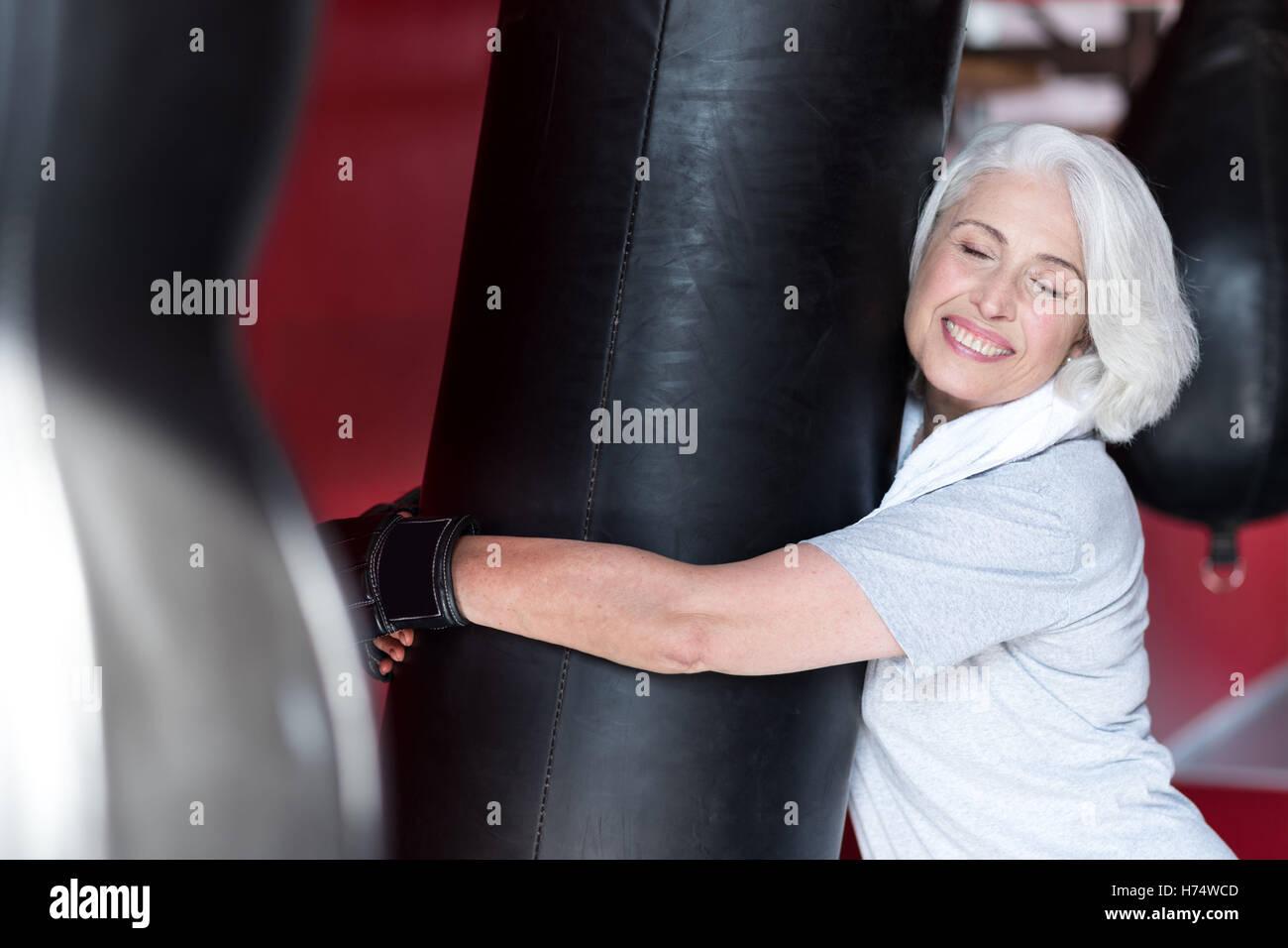 Emotional smiling senior woman hugging punching bag. - Stock Image