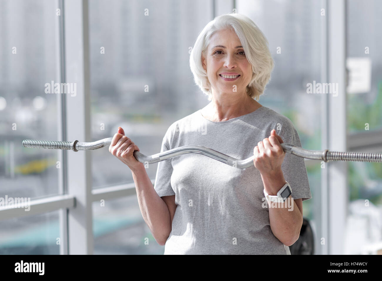 Smiling pretty woman exercising with easy bar. - Stock Image