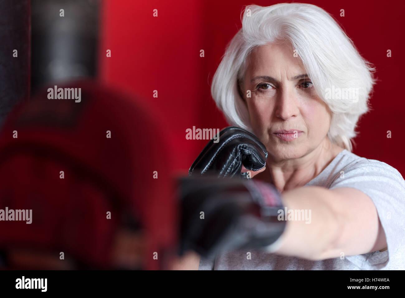 Pretty senior woman boxing punching bag - Stock Image