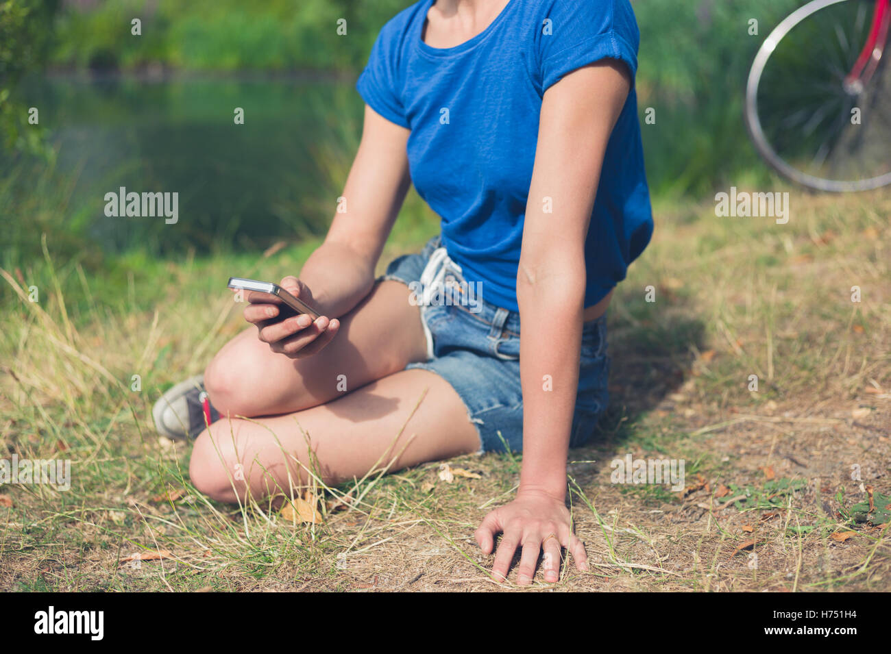 A young woman is sitting by the water in a park and is using a smart phone - Stock Image