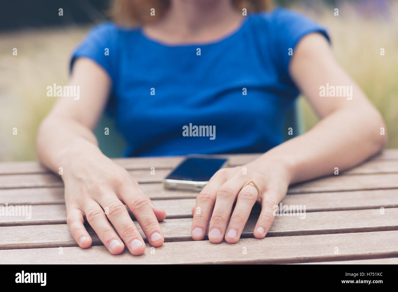 A young woman is sitting at at table outside and is using her smart phone on a summer day - Stock Image