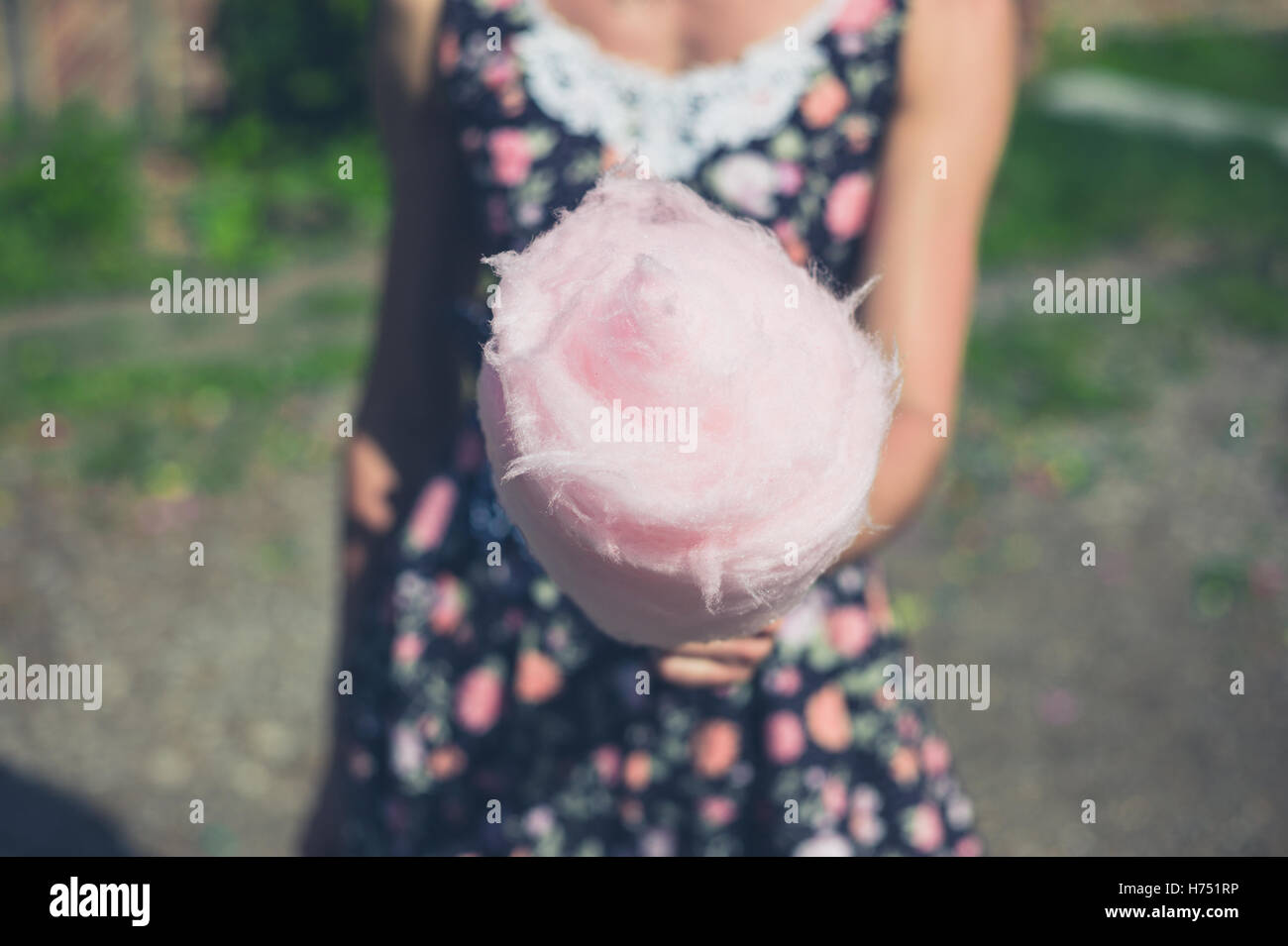 A young woman wearing a dress is standing outside with a candyfloss on a sunny summer day - Stock Image