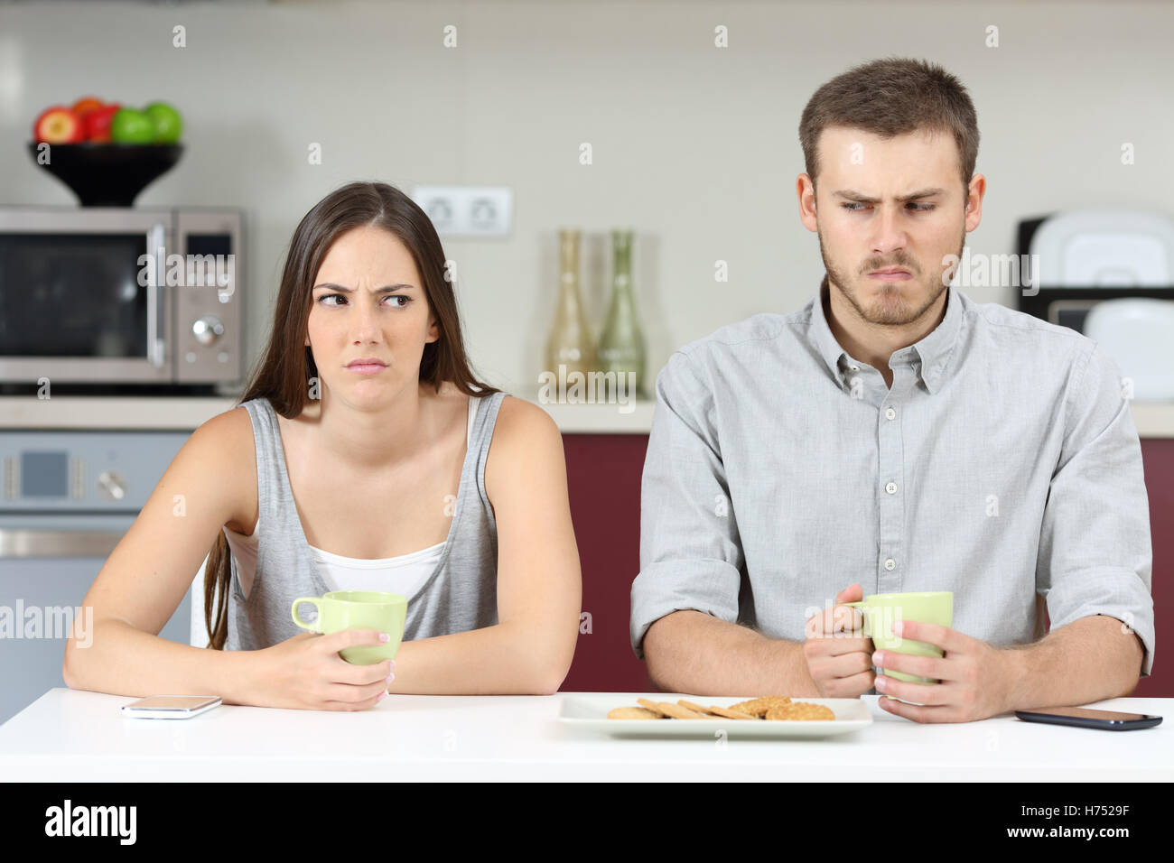 Front view of an angry couple looking each other sideways after argument in the kitchen during breakfast at home - Stock Image