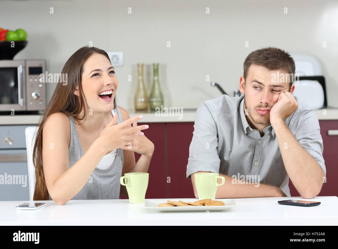 Bored husband hearing his wife talking during breakfast in the kitchen at home - Stock Image