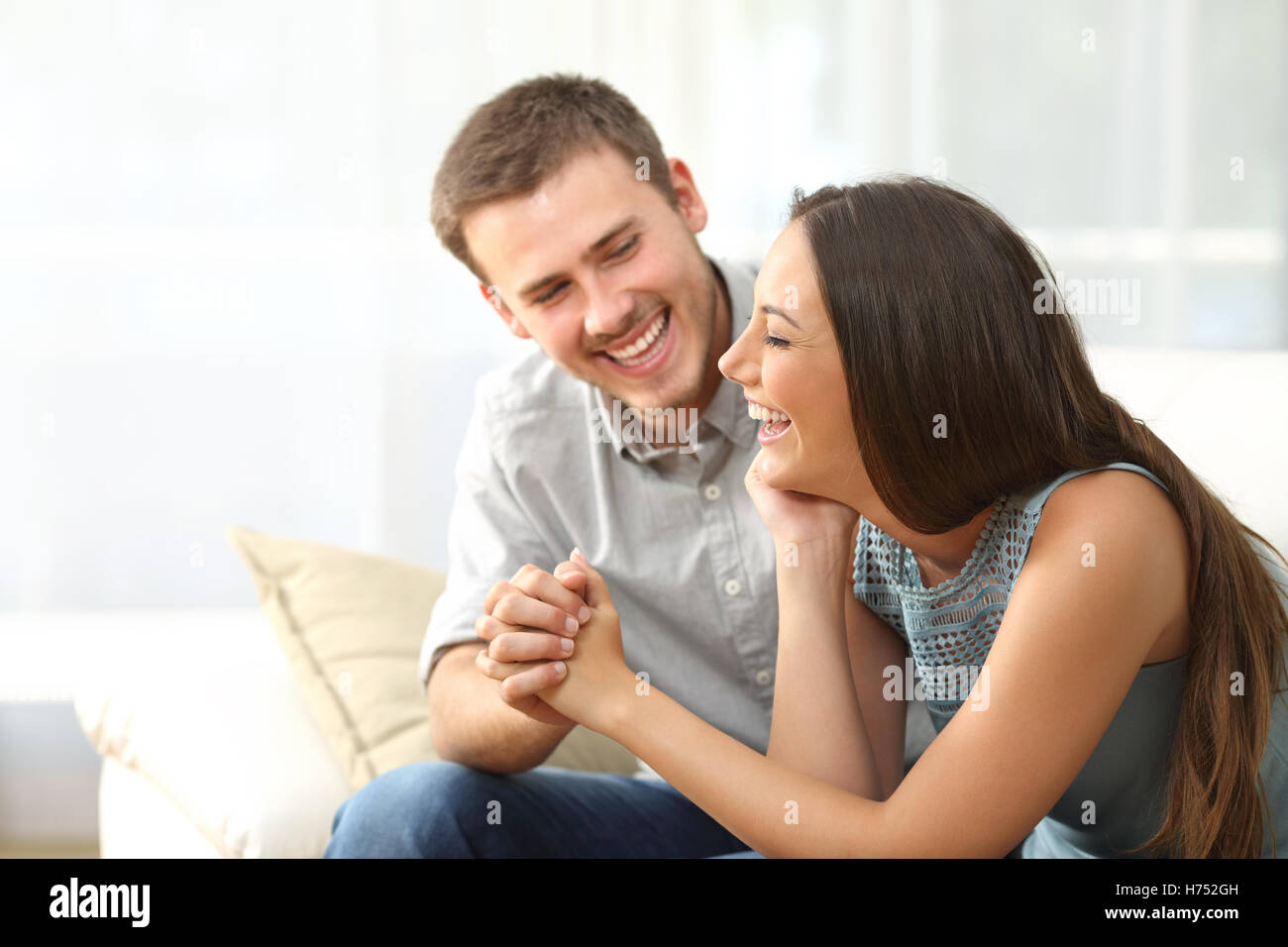 Happy couple or marriage looking each other laughing and holding hands sitting on a sofa at home - Stock Image