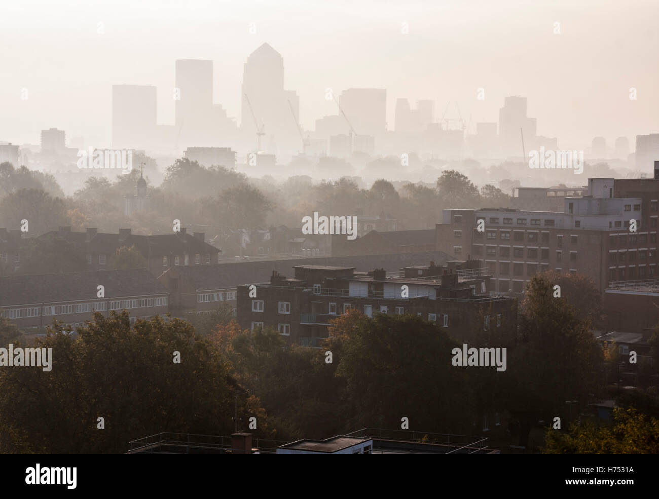 A rooftop view of the foggy London city skyline around Canary Wharf - Stock Image
