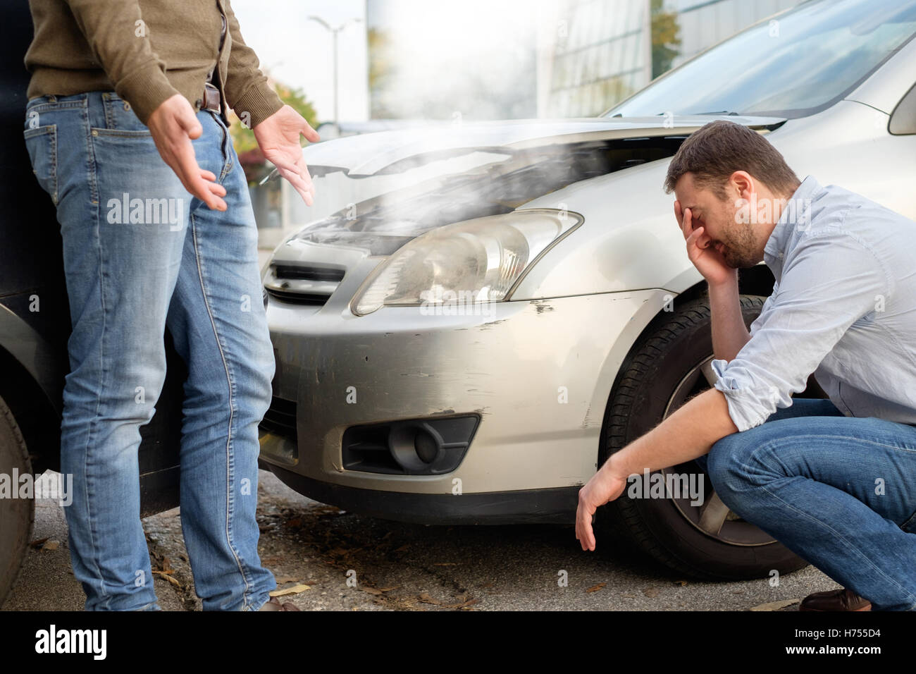 Two men arguing after a car accident on the road - Stock Image