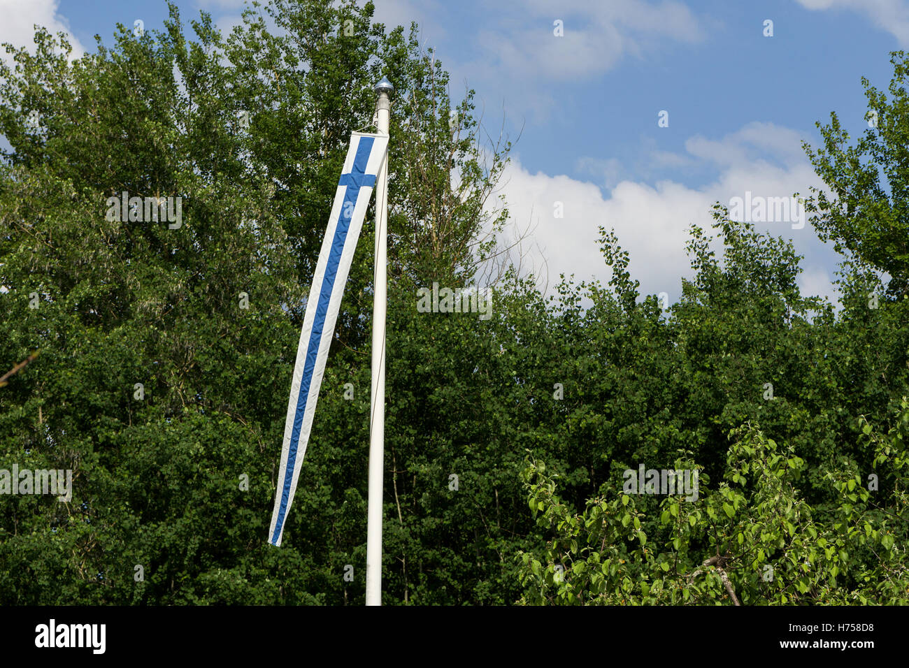 Finland's pennant raised up on a flagpole in the summer. - Stock Image