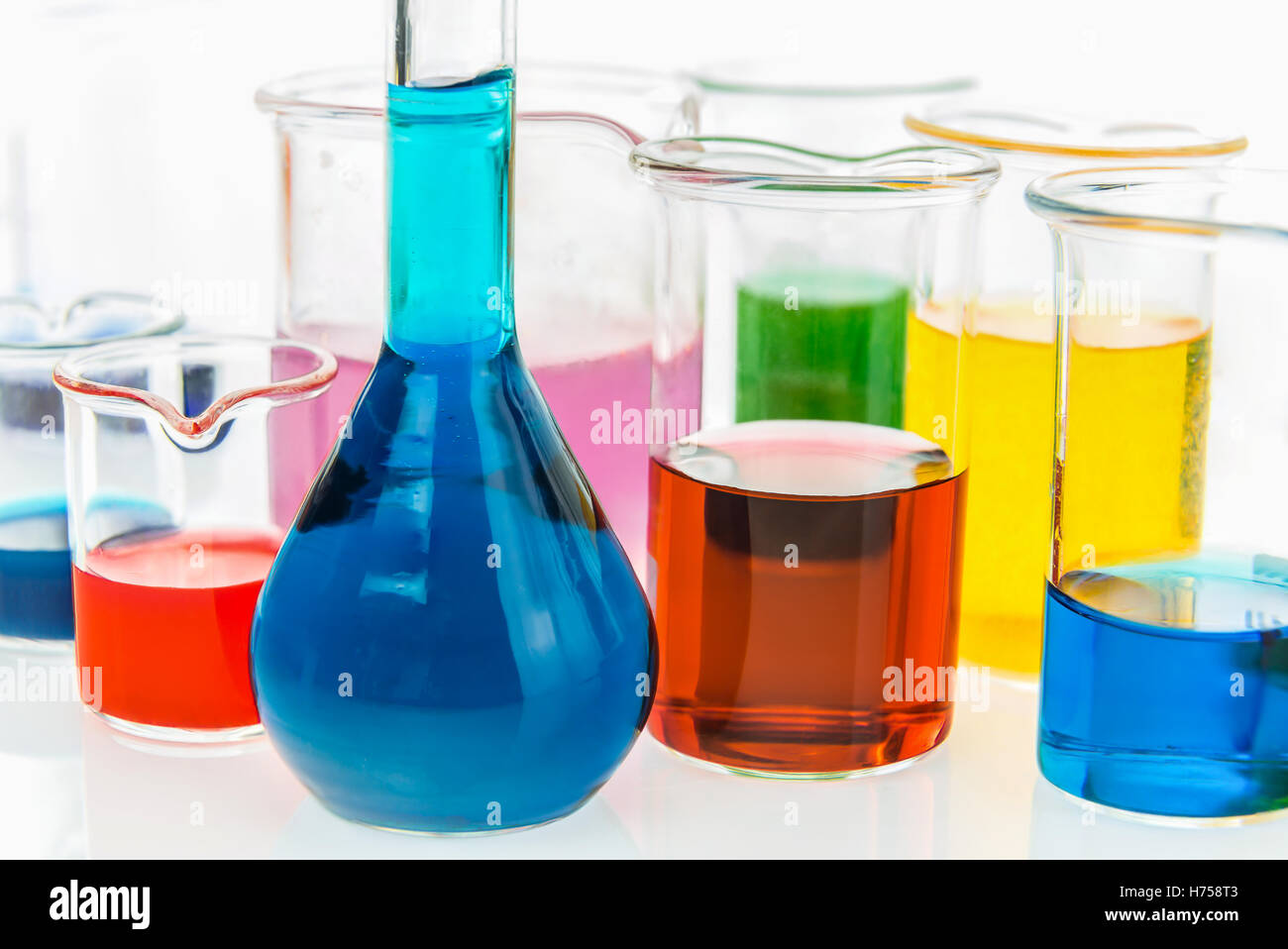 volumetric flask and various beakers with different types of indicators in acids and basis, four colors of indicators Stock Photo