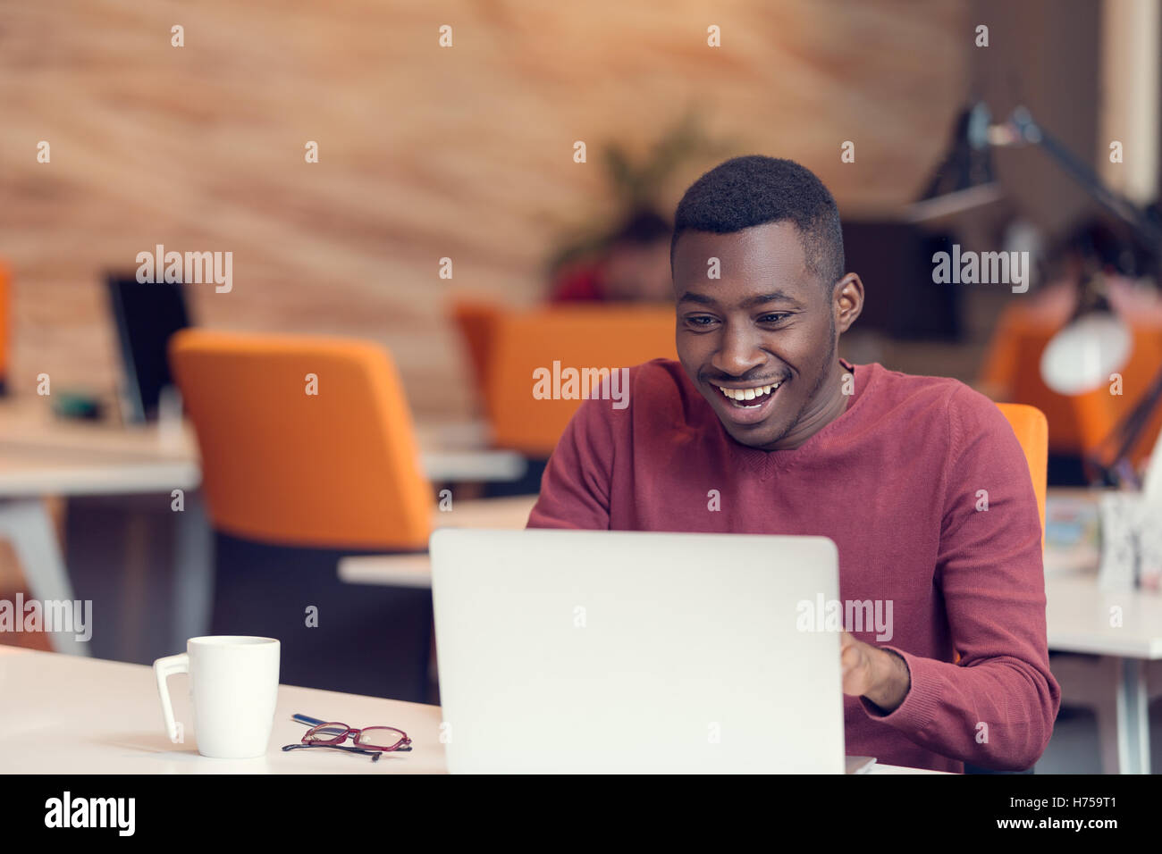 Young business man with a shocked expression working on a laptop - Stock Image