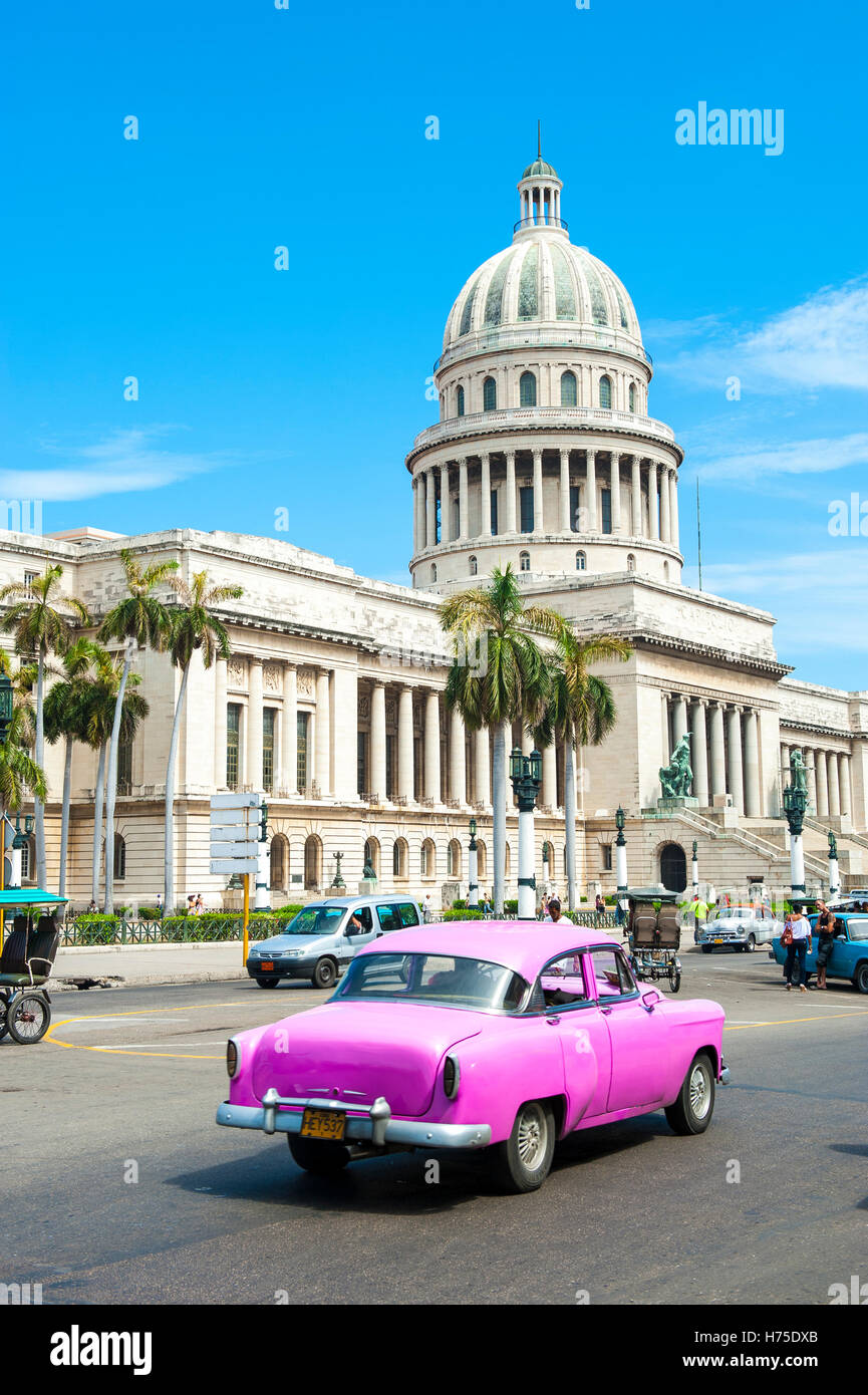 HAVANA - JUNE 17, 2011: Classic American Cuban taxi car passes in front of the Capitolio building in Central Havana. - Stock Image