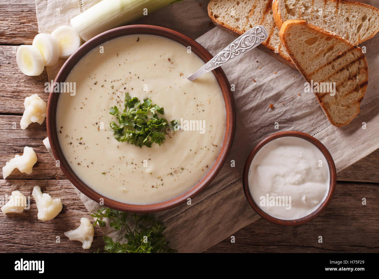 Cauliflower puree soup and ingredients close-up on the table. horizontal view from above - Stock Image