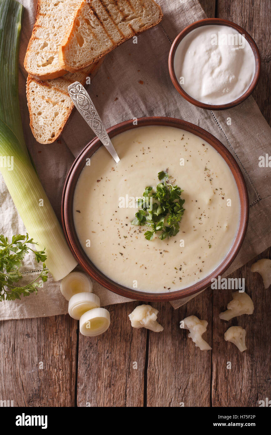 Cauliflower cream soup and ingredients close-up on the table. vertical view from above - Stock Image