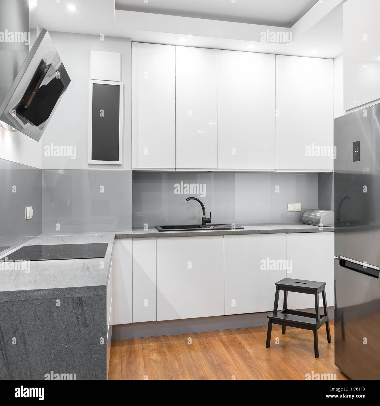 Functional white kitchen with wooden step stool, silver fridge and ...