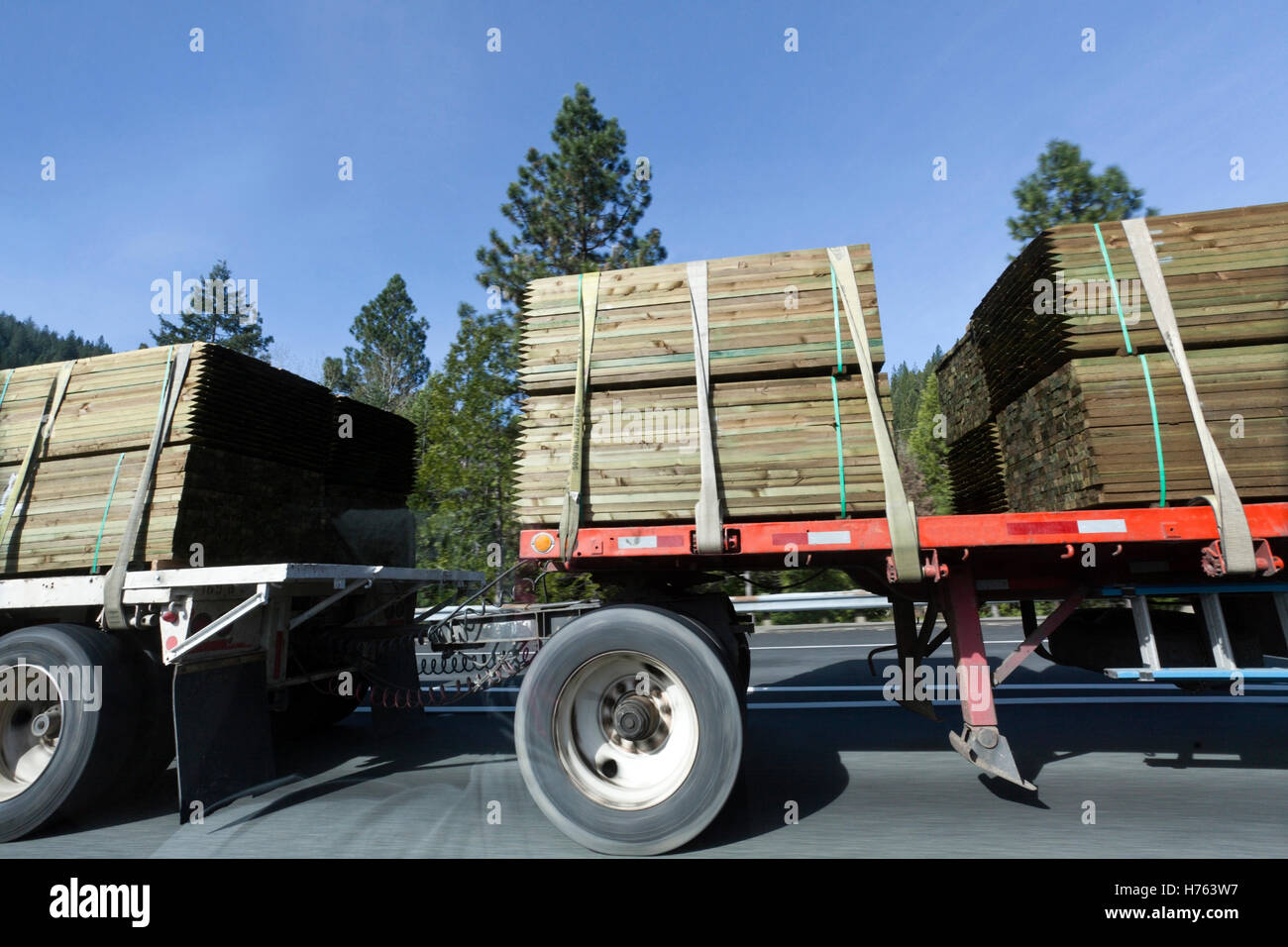 Side view of flatbed hauling, lumber freight - Stock Image