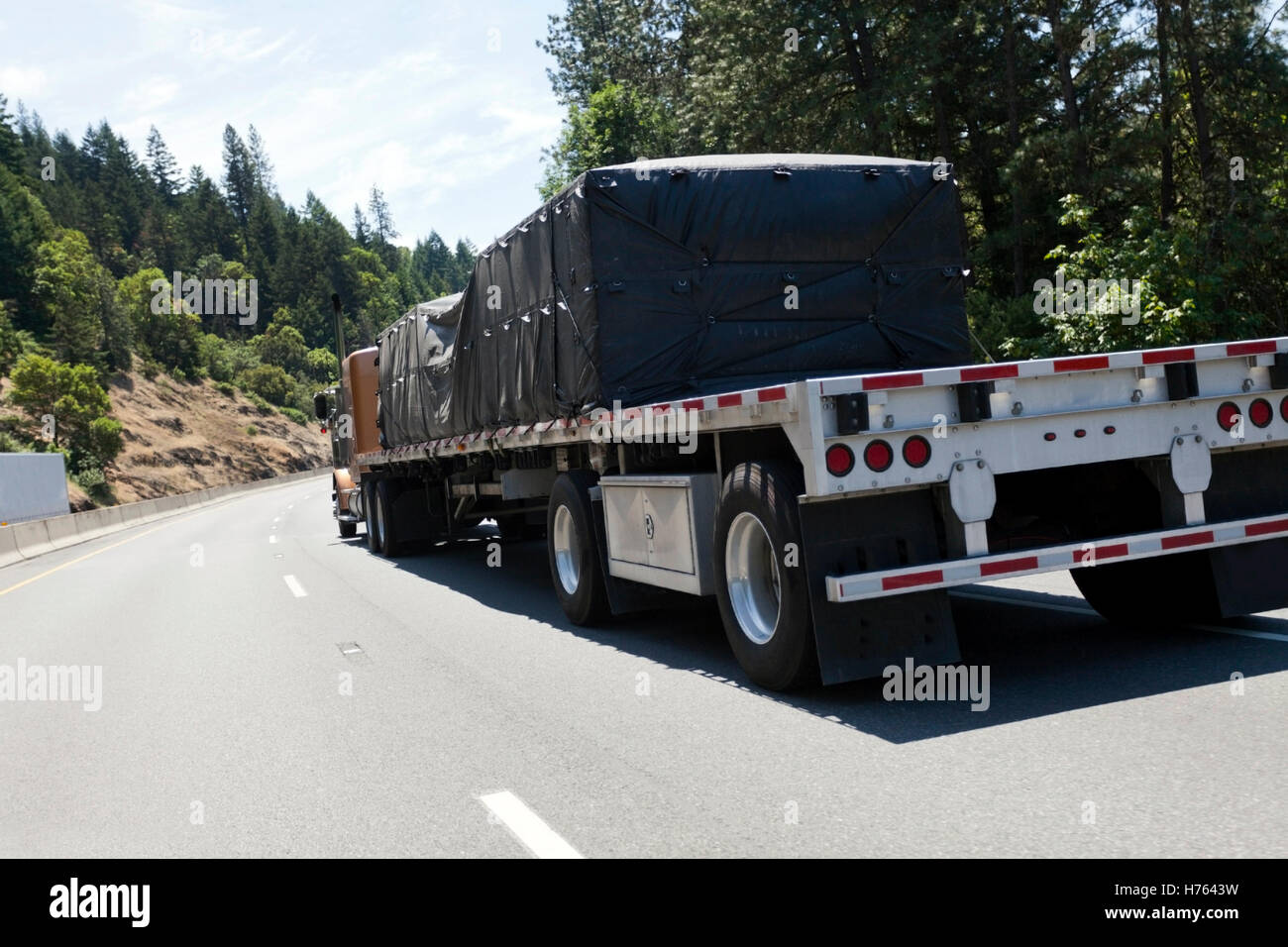 Flatbed trailer hauling tarp-covered freight - Stock Image