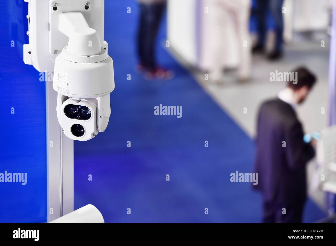 Surveillance camera inside a company with people in the background - Stock Image