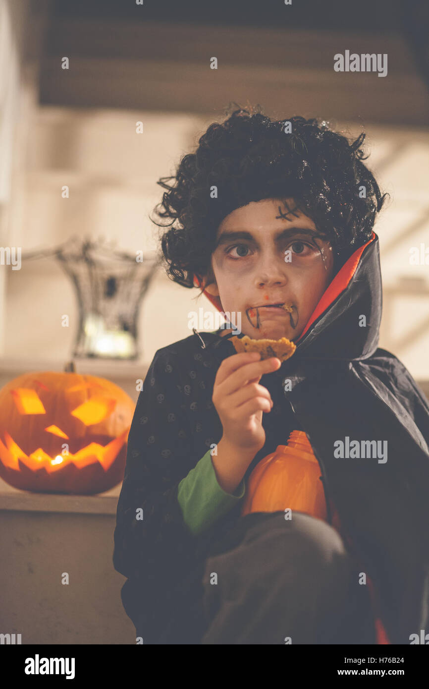Boy dressed in Dracula Halloween costume holding a cookie Stock Photo