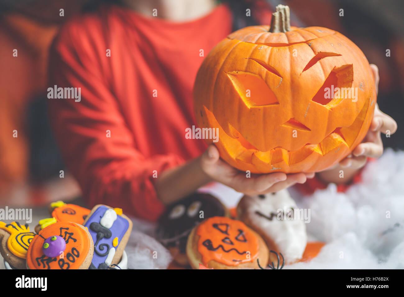 Boy holding a jack-o-lantern halloween pumpkin - Stock Image