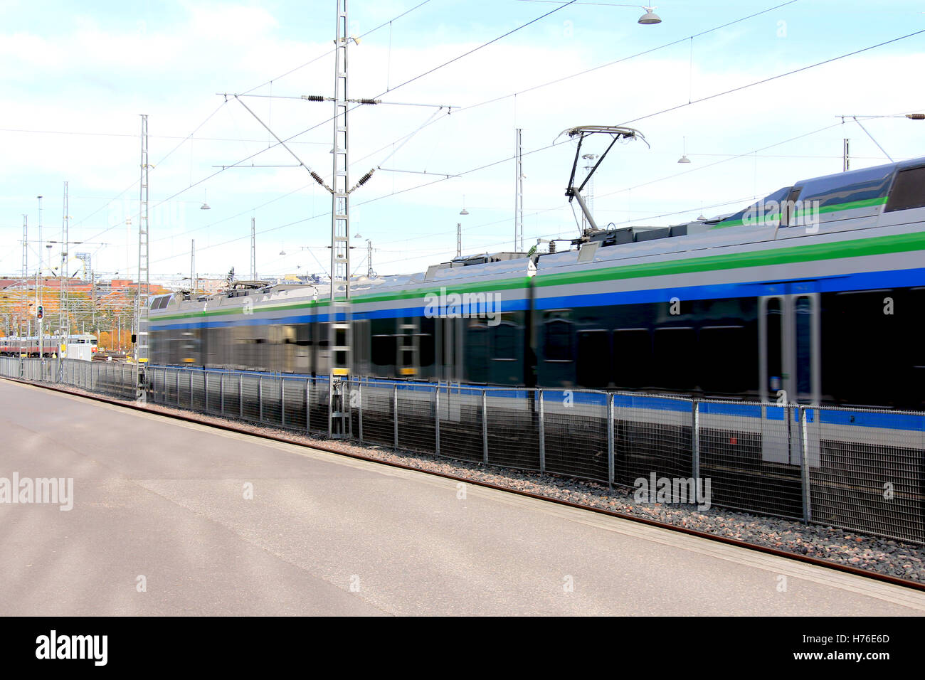 Modern commuter train departs station on a beautiful day. Motion blur. - Stock Image