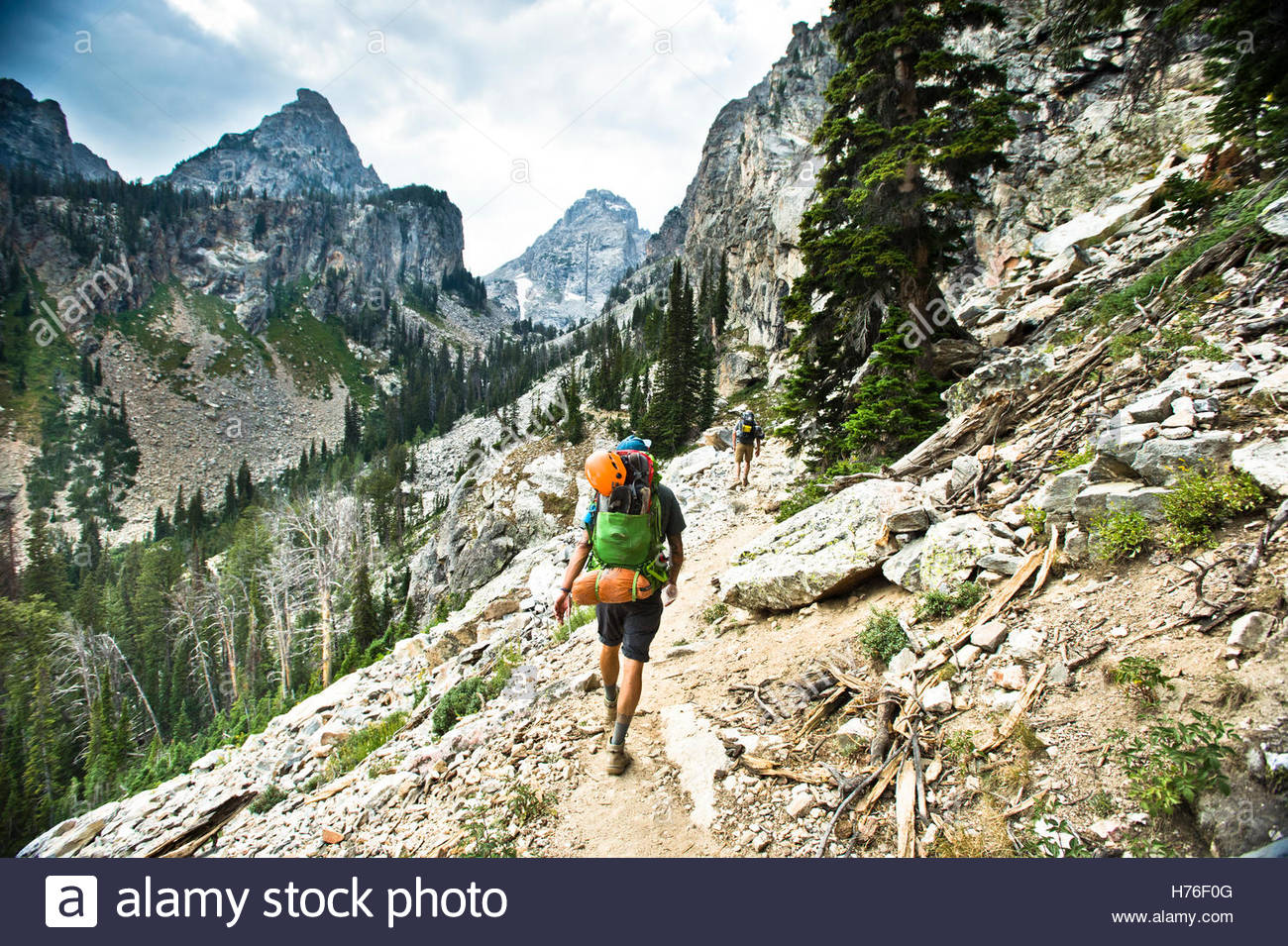 A backpacker going through rocky terrain. - Stock Image