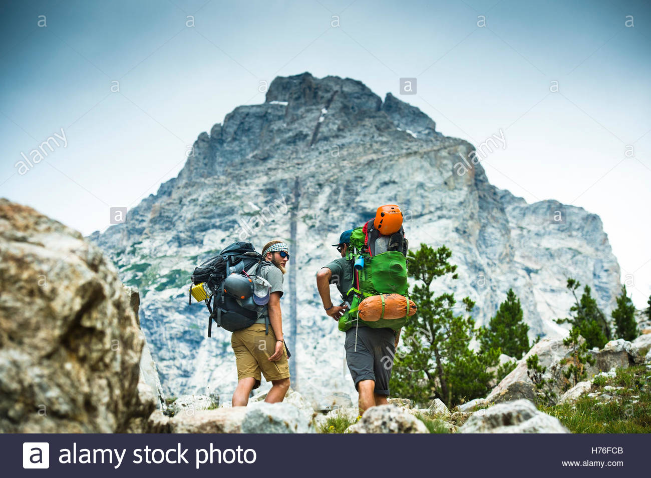 Two hikers stop to take in the mountain views. - Stock Image