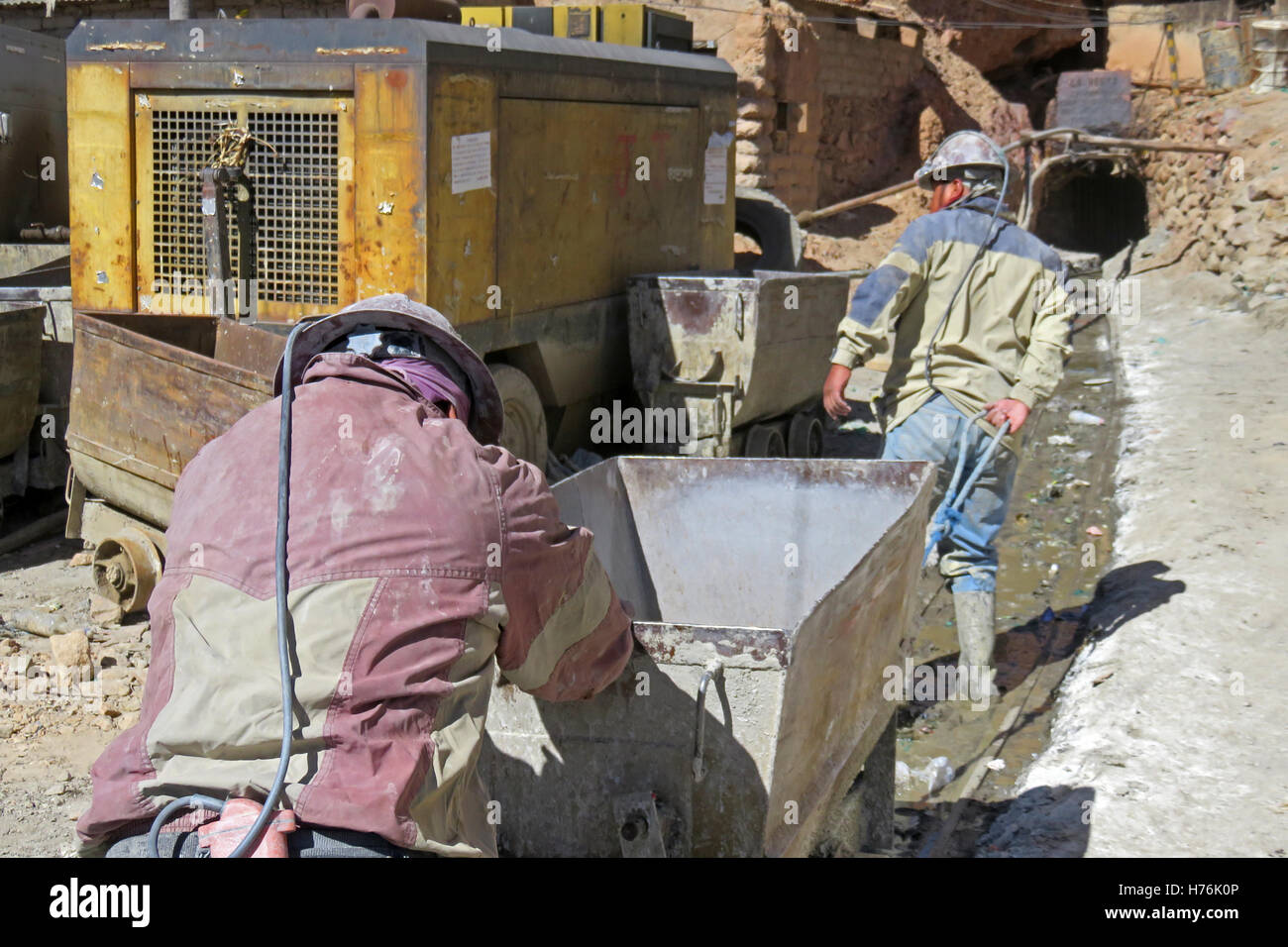 Silver miners pushing the cart into the mines of cerro Rico, Potosi Bolivia - Stock Image