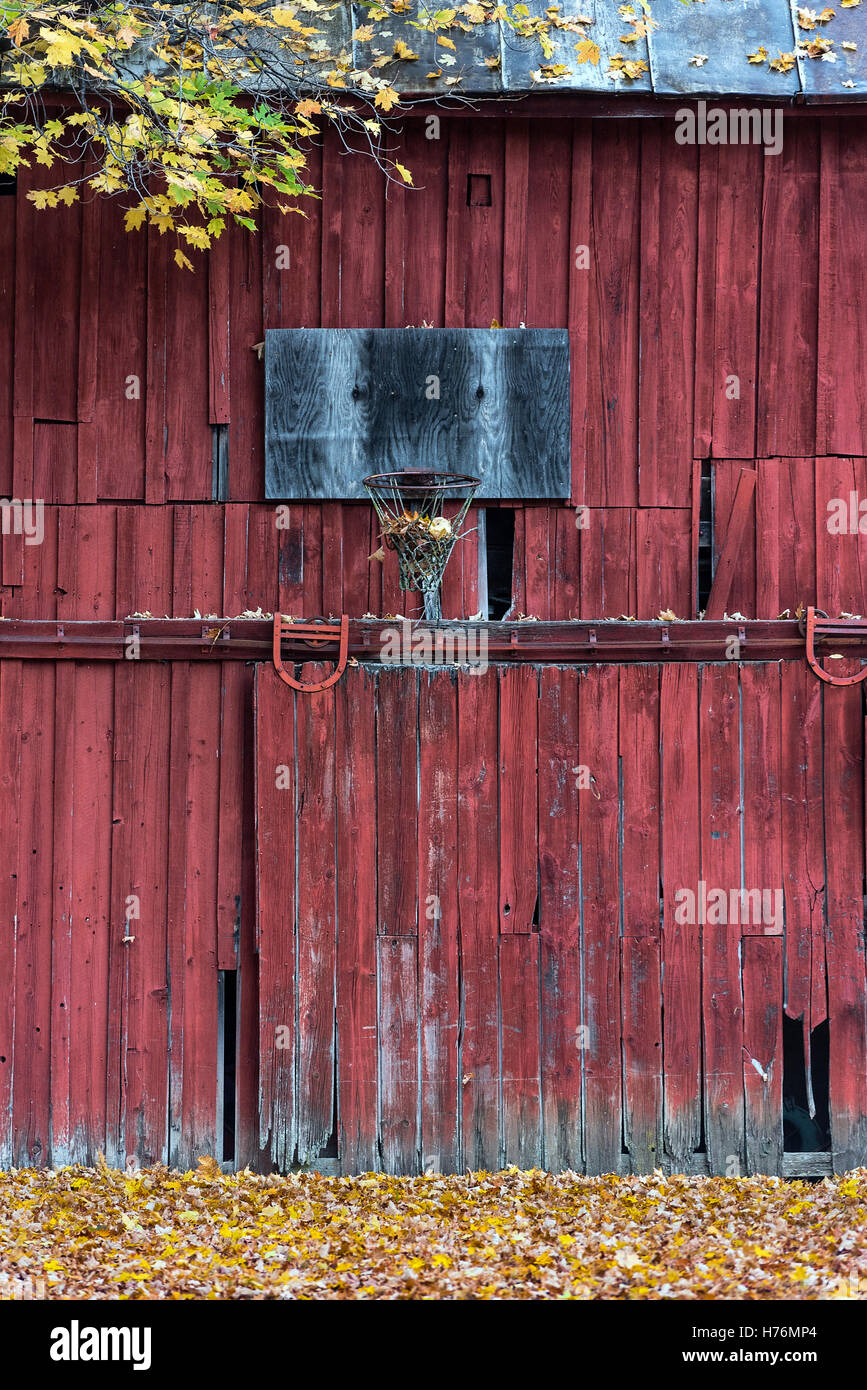 A neglected basketball hoop mounted on a rural red barn, New York, USA. - Stock Image