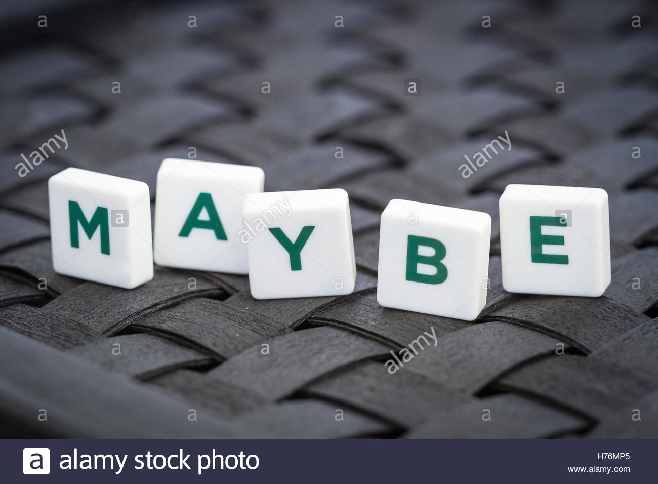 Word 'maybe' made from plastic alphabet blocks, stands in dark background. - Stock Image