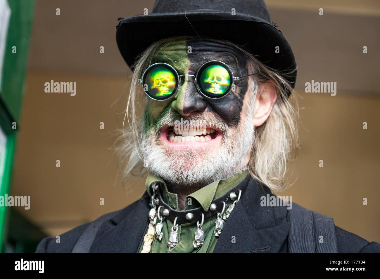 Brooms Bricks and Bowlers Border Morris man. Johnny Morris, face painted black and green, wears hologram sunglasses, - Stock Image