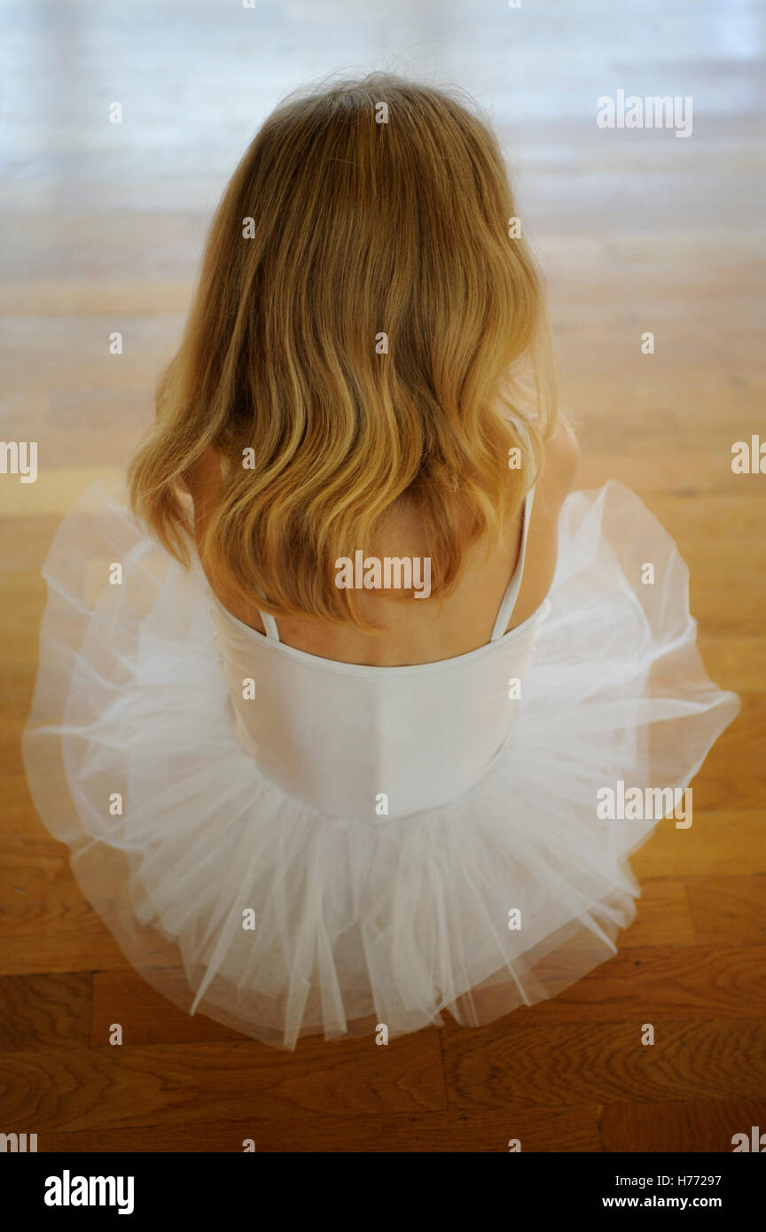 Little ballerina on a wooden floor - Stock Image