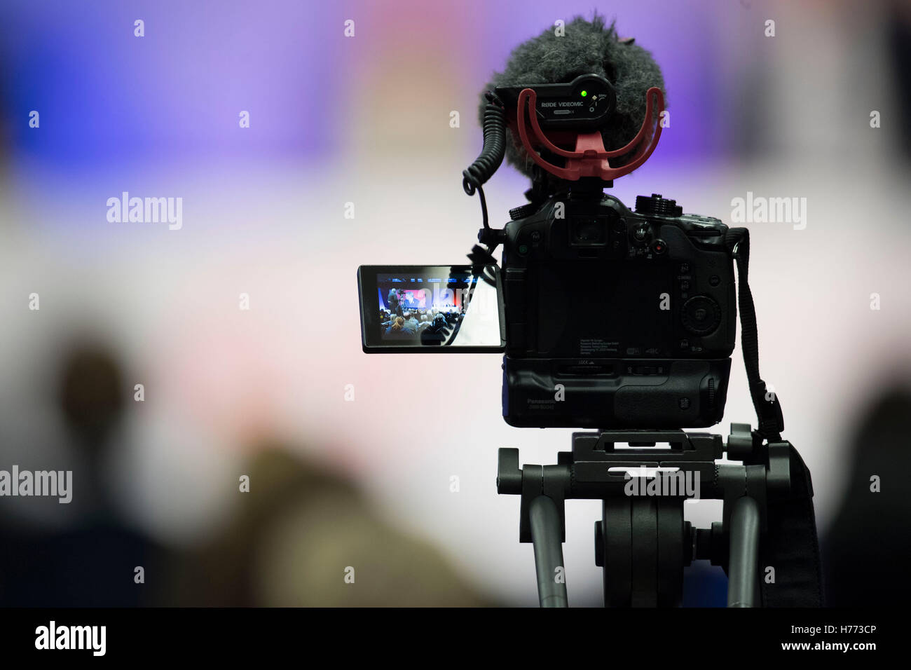 A digital slr video camera on a tripod with microphone recording video at an event - Stock Image