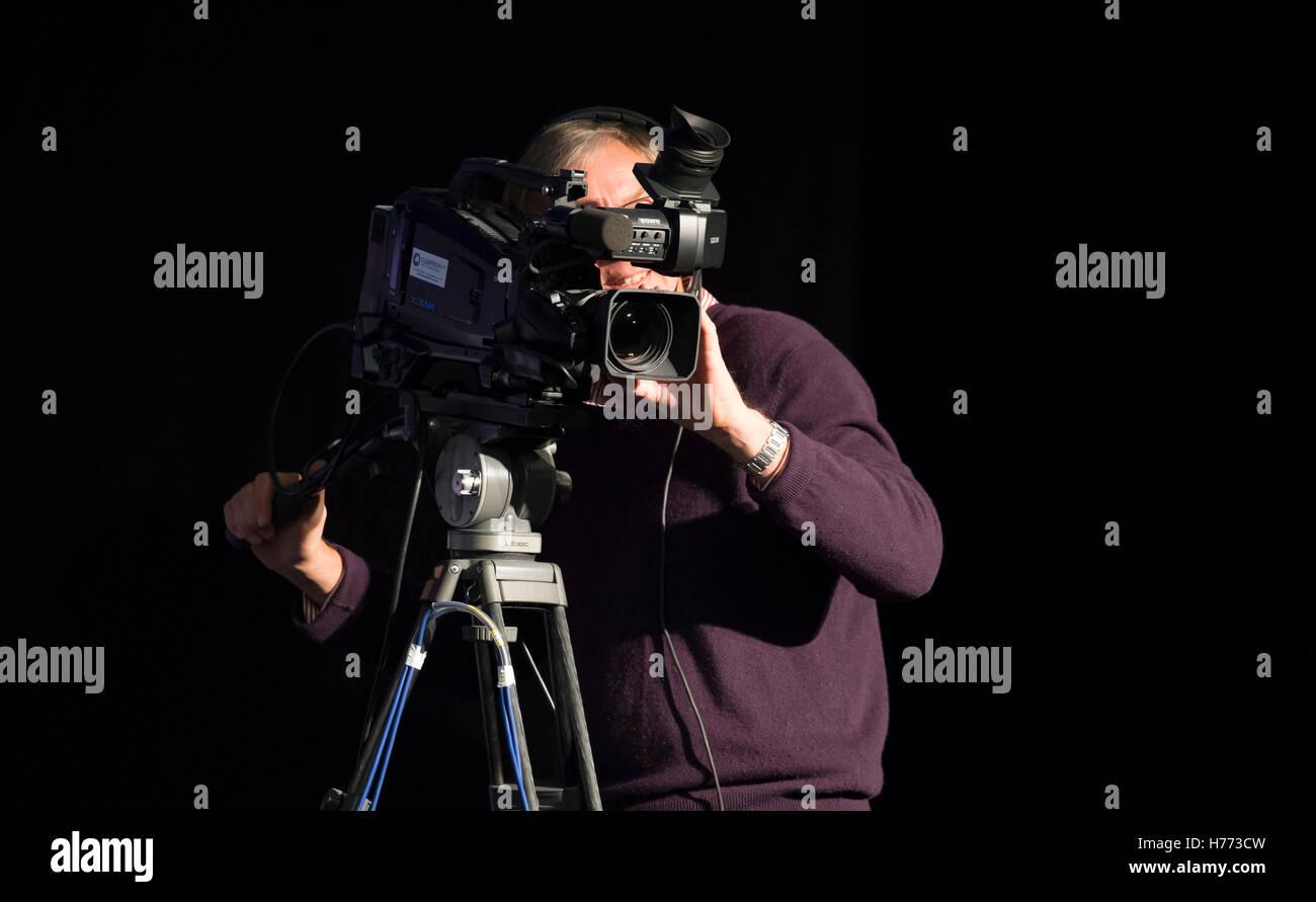 A TV cameraman operating a broadcast camera. - Stock Image