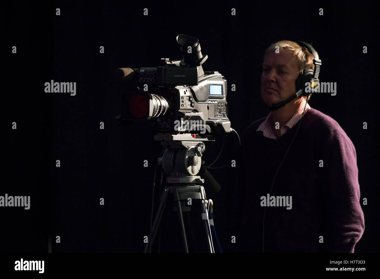 A broadcast tv cameraman using his camera for television recording seen against a black background. - Stock Image