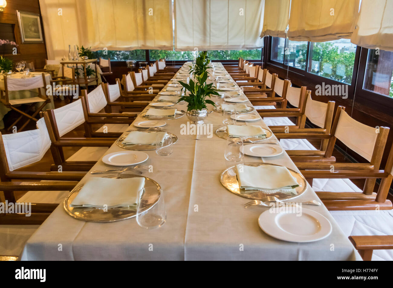 Long Table At An Italian Restaurant With Formal Place Setting For A  Banquet.   Stock