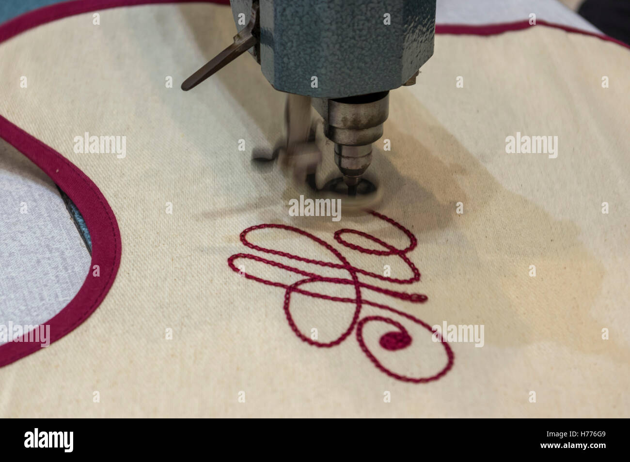 Embroidery of a name in script typeface using a stitching machine. Motion blur of the machine foot. - Stock Image