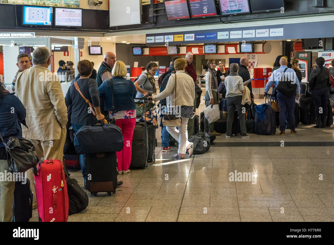 Passengers with baggage queueing up for check-in at the passenger terminal of Genova Cristoforo Colombo international Stock Photo