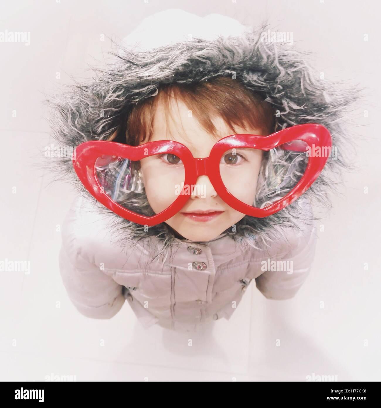 Girl in a warm coat wearing heart shape glasses Stock Photo