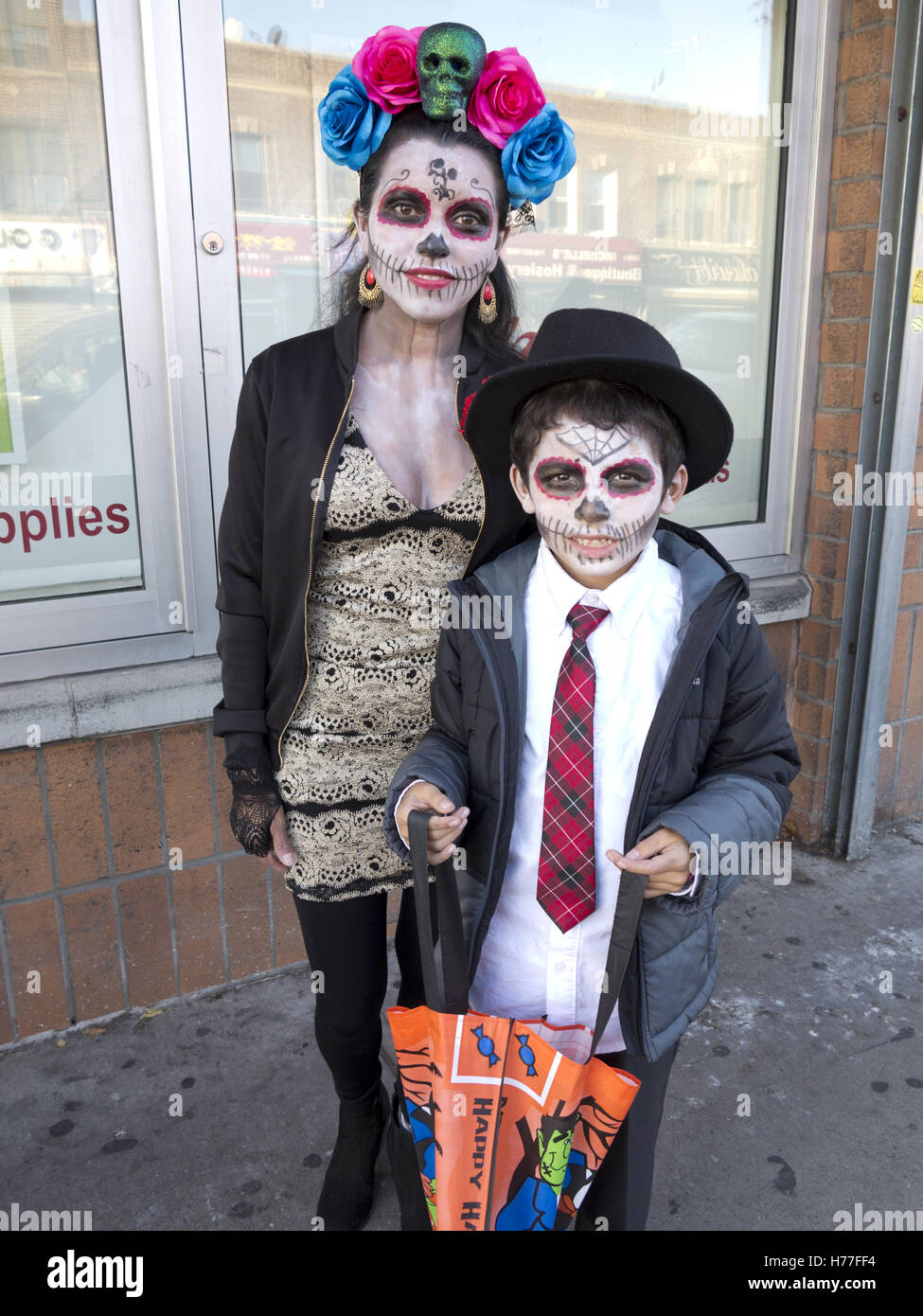 mexican mother and son dressed in day of the dead costumes celebrate