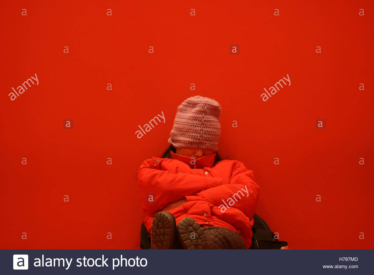 Asian woman in a red jacket naps in a red room - Stock Image