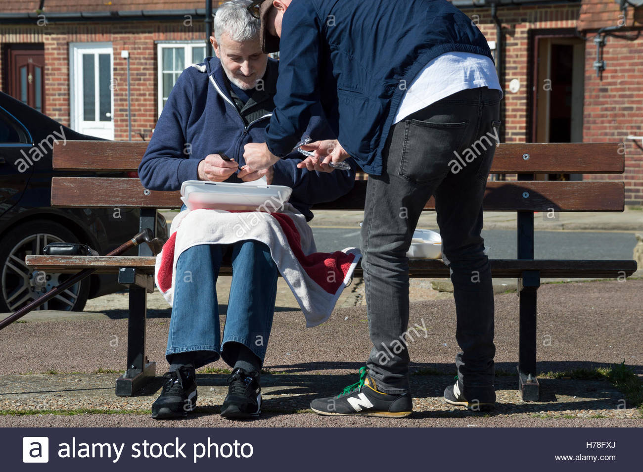 An older man sitting on a bench in the sunshine is helped with his fish and chip lunch by a younger man, Folkestone, - Stock Image