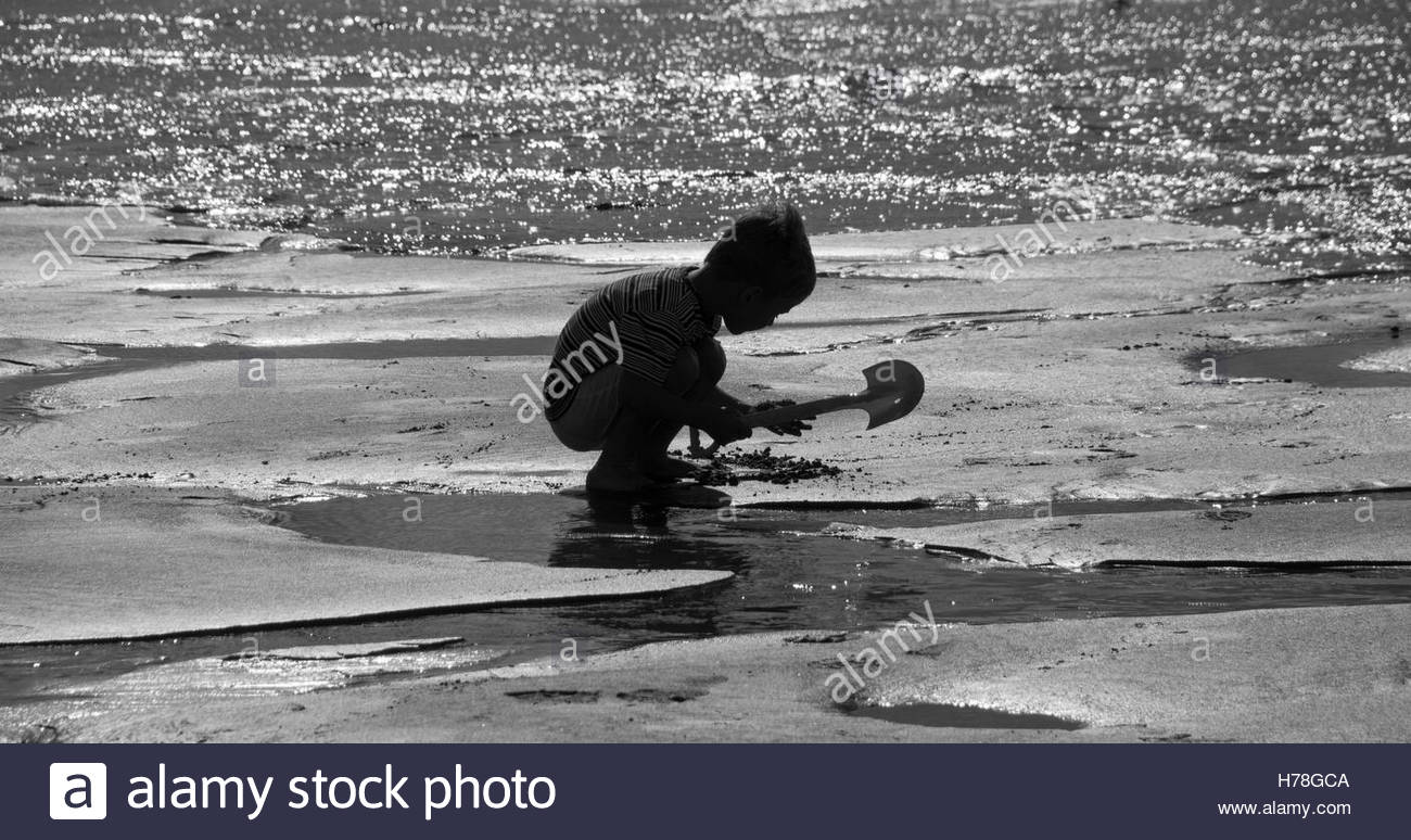 Black and White image of a young boy playing on the beach, Croyde Bay, North Devon, England - Stock Image